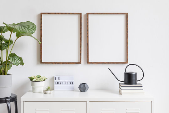 Minimalistic home decor of interior with two brown wooden mock up photo frames on the white shelf with books, black watering can tropical plants, box and home accessories. White walls. Mockup concept.