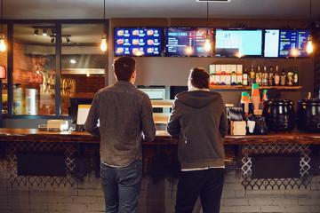 Fototapeta Two men choose food in a fast food restaurant. obraz