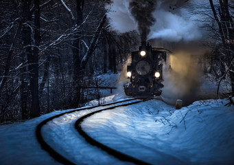 Budapest, Hungary - Beautiful winter forest scene with snow and old steam locomotive on the track in the Hungarian woods of Huvosvolgy at night