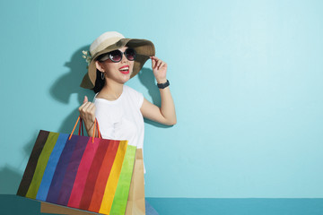 Portrait of beautiful girl holding shopping bags isolated over blue background.