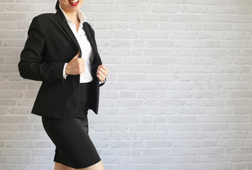 Pretty girl in black suit standing and smiling in her office. body part