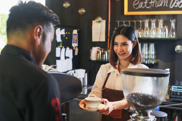 Young female barista serving coffee to customer in cafe.