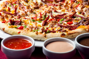 Delicious pizza with with sauces on the table. Food concept