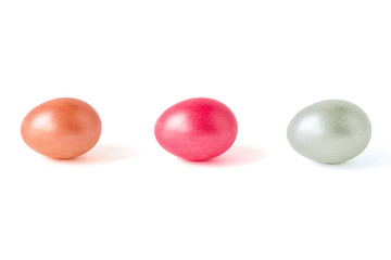 The eggs of three colors isolated on a white background. Pink, orange, silver