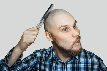 Bald funny guy with a beard and a comb in his hands, combing his head and beard in the morning at home on a colored background. Concept: humor, absurdity Wall mural