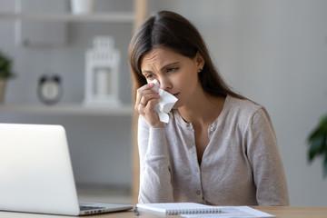 Upset woman crying, looking at laptop screen, watching sad movie