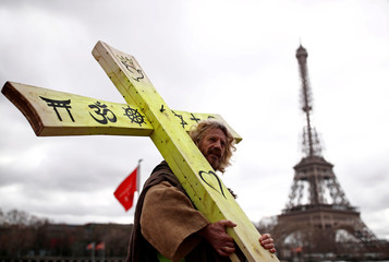 """A protester wearing a yellow vest holds a cross as he walks past the Eiffel tower during a demonstration by the """"yellow vests"""" movement in Paris"""