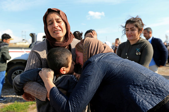 Relatives hug a Yazidi survivor boy following his release from Islamic State militants in Syria, in Duhok