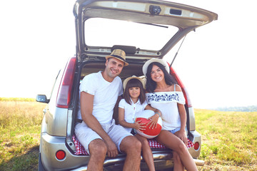 A happy family has a car on a summer trip.