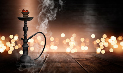 Hookah in a dark room with smoke, abstract bokeh light, wooden table, wet asphalt, reflection.