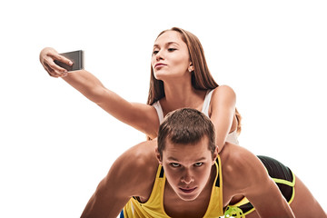 Athletic man doing push-ups while his girlfriendd making selfie
