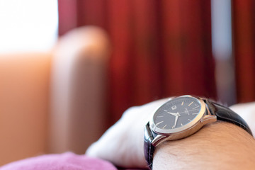 Close-up of hand with watch in hotel room