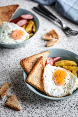 Breakfast with French fries, fried egg, sausage and toast on the table