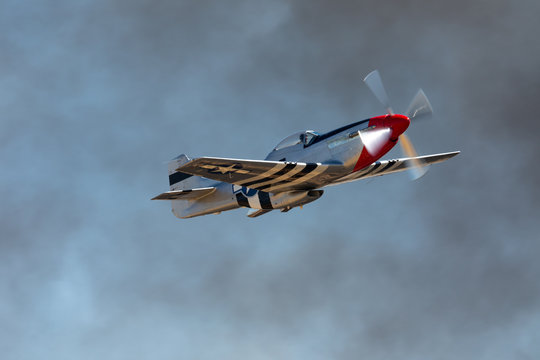 P51D Mustang (WWII American fighter plane) in beautiful light, against smoke