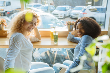 Multi-cultural and difference of cultures, friendship concept. Two curly multiracial female friends talking drinking fresh smoothies or juice in cafe interior over window on backround. Side view