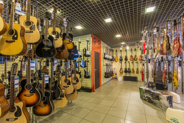 Tuinposter Muziekwinkel A row of different electric guitars hanging in a modern musical shop