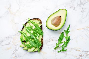 Arugula avocado rye breakfast sandwich