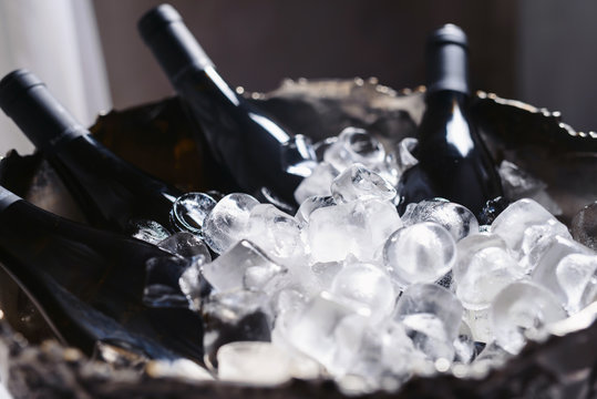 Closeup and selective focus of wine and champagne bottles chilling in a bucket full of ice.