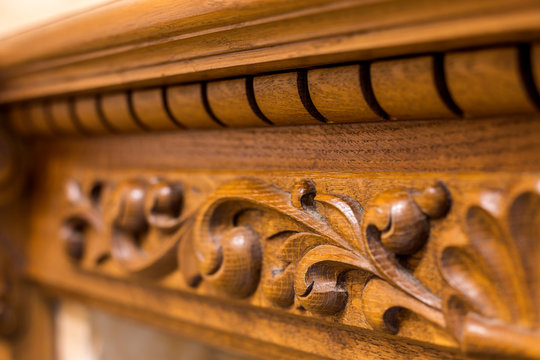 Close-up detail of carved wooden decorative piece of furniture with floral ornament made of natural hardwood. Art craft and design concept.