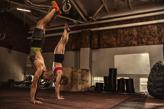 Athletic young couple doing a handstand at the gym