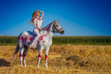 Blonde girl in white and red bodypaint jumps over the field with a white horse