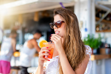 Attraktive, blonde Frau im Sommer Urlaub genießt einen Cocktail an einer Strandbar