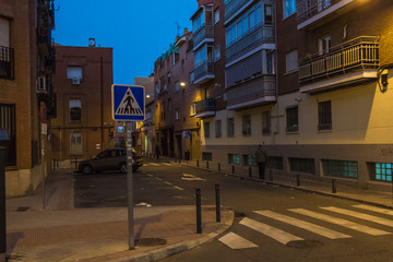 Night scene of a street in urban Madrid with several apartment buildings