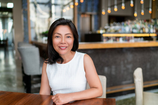 Asian middle age business woman smiling portrait. Happy elegant mature Chinese businesswoman lady in fancy restaurant setting.