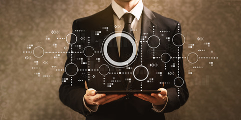 Connected circles chart with businessman holding a tablet computer on a dark vintage background
