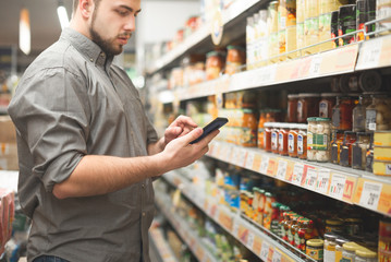 Man is in the department of canned vegetable supermarket and uses a smartphone. Buyer looks at the shopping list on the smartphone. Purchase of food at the grocery store.