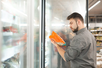 Buyer standing in the supermarket near the refrigerator holds the package in his hand and reads the...