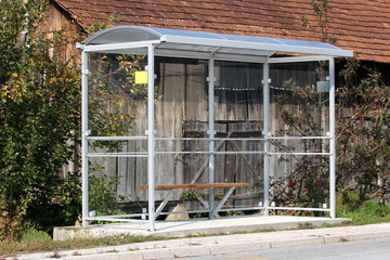 Printed roller blinds Old abandoned buildings Bus station made of strong metal and clear glass with wooden bench on concrete foundation next to paved road surrounded with trees and wooden barn in background on warm sunny day