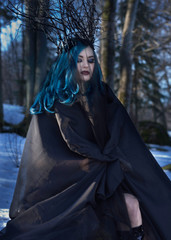 Black queen. Blue hair woman portrait in forest.