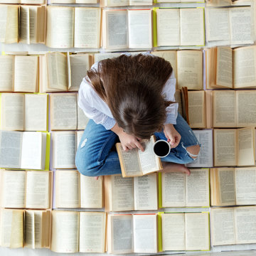 A young student reads a book and drinks coffee. Top view. Concept for World Book Day, lifestyle, study, education.