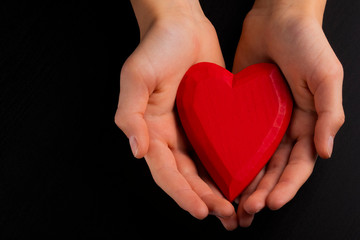 Hands of a teenager child holding a red wooden heart in their hands.