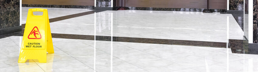 Marble shiny floor in a luxury hallway of company or hotel during cleaning. Panorama of a washed cleaned floor with sign of caution wet floor. Professional care service of the office interior.