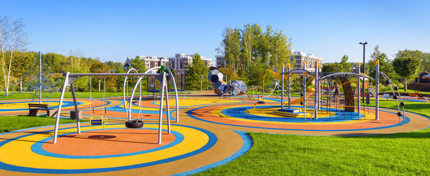 Panorama of colorful large playground in city park. Empty modern outdoor playground in summer. Beautiful urban place for kids games and sport. Scenic view of children ground.