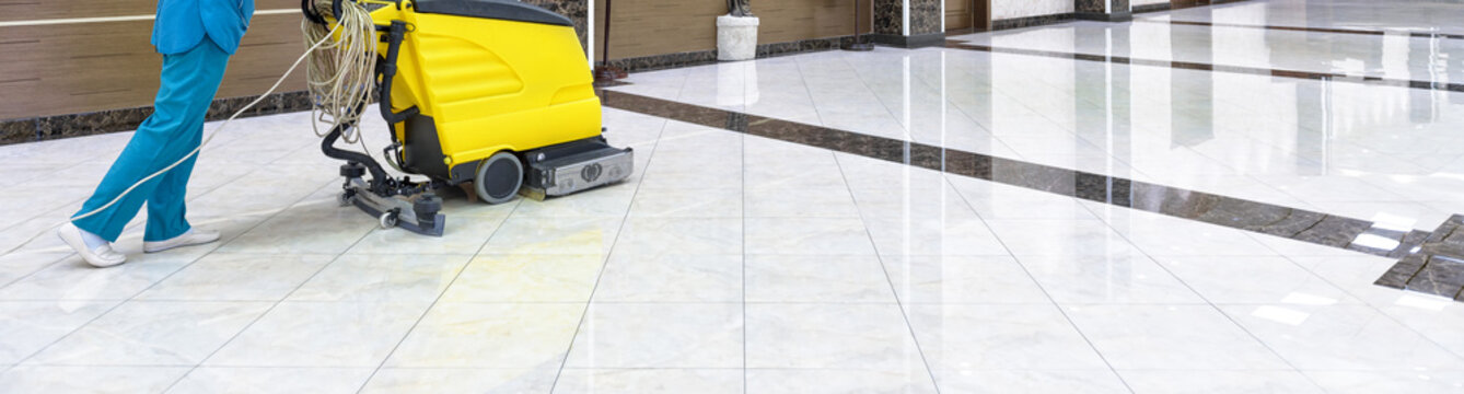 Floor care with washing machine in office lobby. Panorama of cleaning service with vacuum equipment on shiny marble floor in the luxury interior of company. Concept of professional cleaning job.