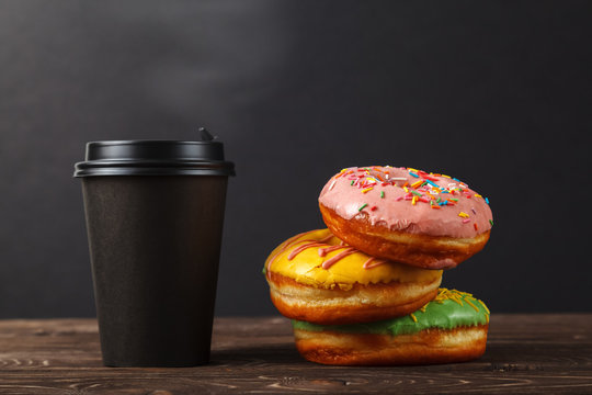 Colorful donuts and coffee in a black paper Cup on a black background. Bakery menu design concept. Hanukkah background.
