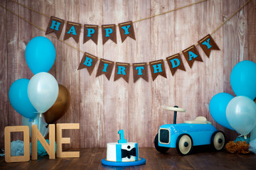 Photoshoot crush smashcake for a little boy gentleman. Decorated photozone with a wooden retro car and helium balloons. Happy birthday, 1 year