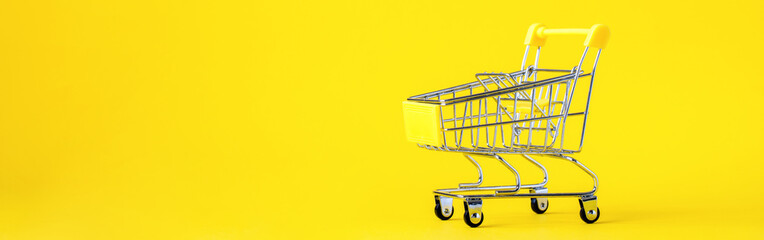 Shopping cart trolley basket is empty on a bright yellow background. Conception Festive Sale Discount. Trading Supermarket Retail.Copy space .Banner.