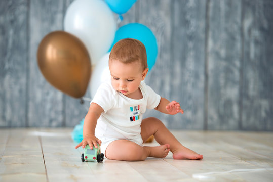 Cute little boy 1 year old sits on a warm wooden floor and plays with a toy car. Behind the plan birthday balloons