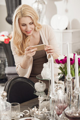 Mature woman talkign photos of flowers at the store