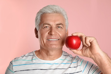 Mature man with healthy teeth and apple on color background