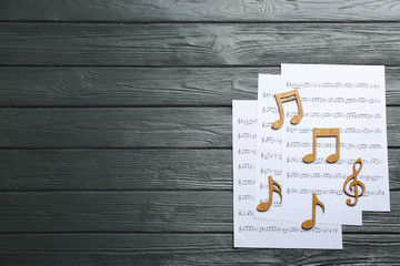 Sheets and music notes on wooden background, top view. Space for text