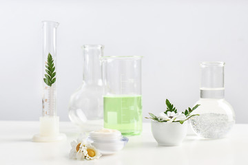 Skin care product, ingredients and laboratory glassware on table. Dermatology research