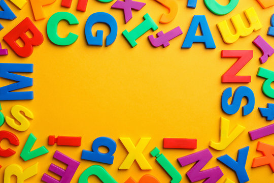 Frame made of plastic magnetic letters on color background, top view with space for text