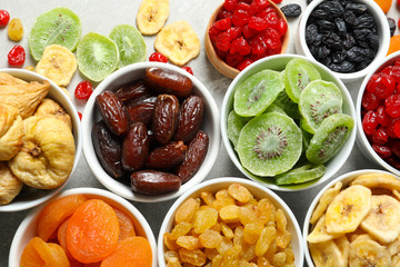 Bowls with different dried fruits on grey background, flat lay. Healthy food