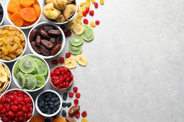 Bowls of different dried fruits on grey background, top view with space for text. Healthy food