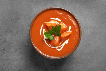Bowl of delicious butter chicken on grey background, top view. Traditional indian Murgh Makhani